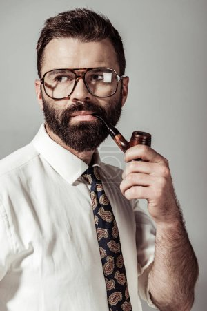Foto de Guapo con barba hombre gafas, camisa y corbata pipa aislada en gris - Imagen libre de derechos