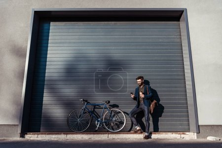 Photo for Handsome bearded man in glasses standing near bicycle - Royalty Free Image