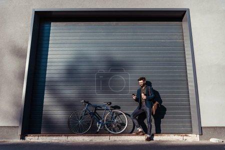 Photo pour Bel homme barbu dans des verres debout près de bicyclette - image libre de droit