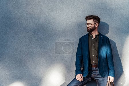 Photo for Handsome bearded man in glasses and cap standing near wall - Royalty Free Image