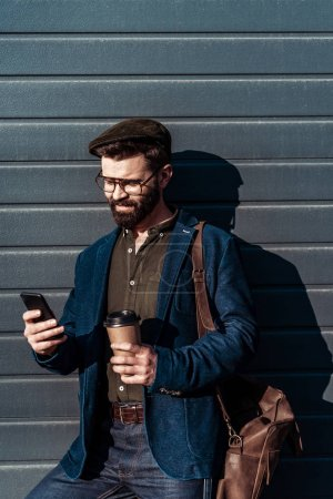 Photo for Handsome bearded man in glasses and cap holding paper cup and using smartphone - Royalty Free Image