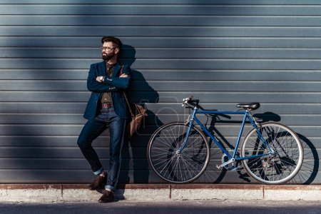 Photo for Handsome bearded man in glasses and cap posing near bicycle - Royalty Free Image