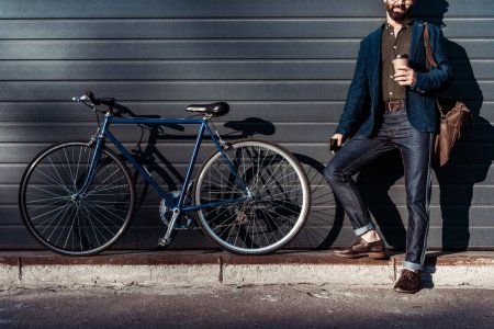 Photo for Bearded man and cap holding cup and standing near bicycle - Royalty Free Image