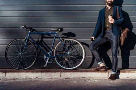 Photo pour Homme barbu et cap holding coupe et debout près de bicyclette - image libre de droit