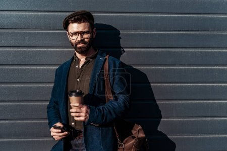 Photo for Handsome bearded man in glasses and cap holding paper cup and smartphone - Royalty Free Image