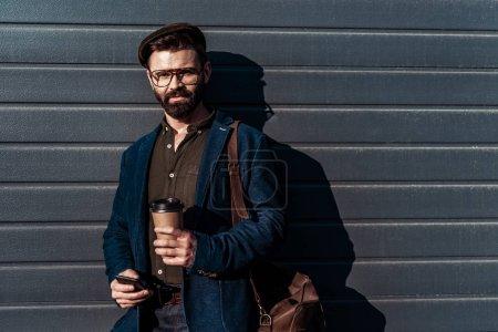 Foto de Guapo hombre barbudo en gafas y gorra con smartphone y taza de papel - Imagen libre de derechos