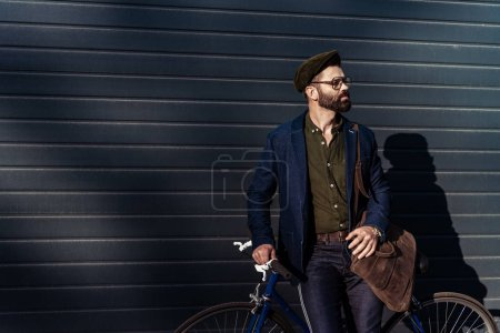 Photo for Handsome bearded man in glasses and cap holding bicycle - Royalty Free Image