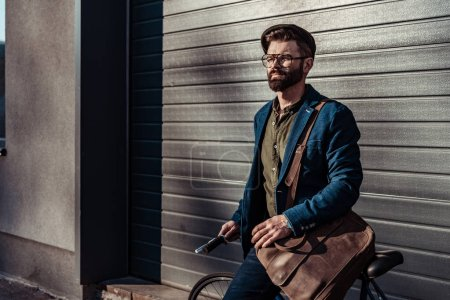 Photo for Handsome bearded man in glasses and cap holding bicycle and smiling - Royalty Free Image