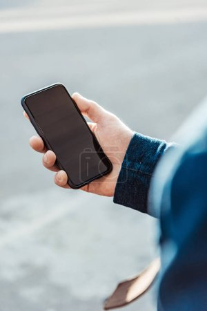 Photo for Cropped view of man holding smartphone with blank screen - Royalty Free Image