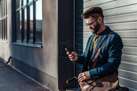 Photo for Handsome bearded man in glasses and cap holding bicycle and looking at smartphone - Royalty Free Image