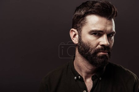Photo for Handsome bearded man in brown shirt looking at camera isolated on brown - Royalty Free Image