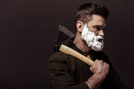Foto de Hombre barbudo guapo con espuma de afeitar en la cara que sostiene el hacha aislado en marrón - Imagen libre de derechos