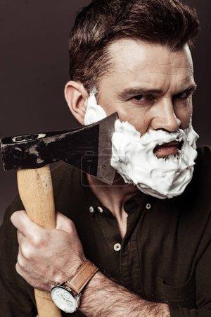 Foto de Hombre guapo serio con espuma en la cara barba de afeitar con hacha aislada en marrón - Imagen libre de derechos