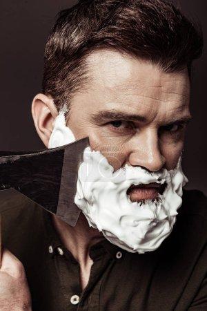Foto de Primer plano de hombre barbudo guapo serio afeitándose con hacha mientras mira la cámara aislada en marrón - Imagen libre de derechos