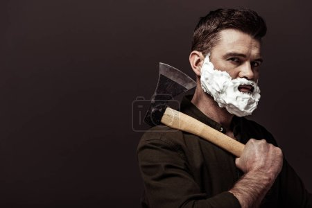 Foto de Hombre barbudo guapo en camisa marrón sosteniendo hacha y mirando a la cámara aislada en marrón - Imagen libre de derechos