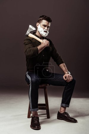 Foto de Hombre barbudo guapo sentado en la silla y sosteniendo hacha - Imagen libre de derechos