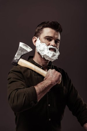 Foto de Hombre barbudo guapo en camisa marrón sosteniendo hacha mientras mira la cámara aislada en marrón - Imagen libre de derechos