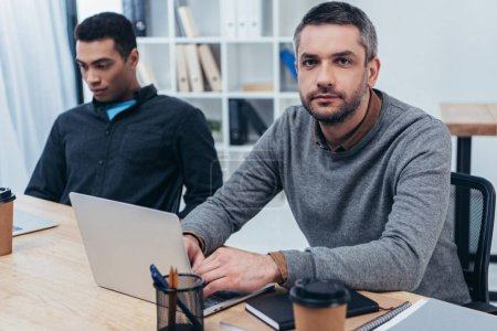 Photo for Serious businessman using laptop and looking at camera while working with young colleague in office - Royalty Free Image