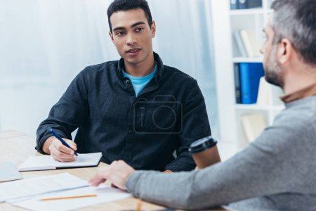 Photo pour Jeune entrepreneur écrire dans cahier et regardant collègue assis dans le bureau - image libre de droit