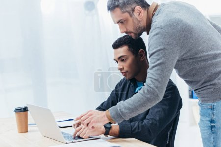 Photo for Bearded mentor helping young colleague working with laptop in office - Royalty Free Image