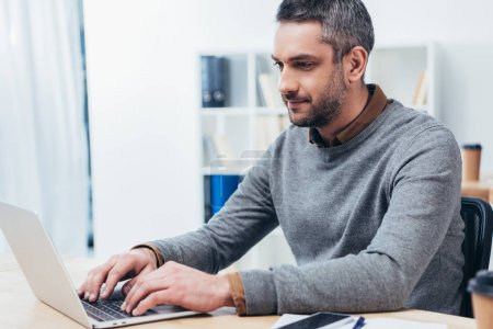 Photo for Handsome smiling bearded businessman working with laptop in office - Royalty Free Image