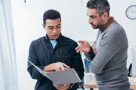Photo pour Hommes d'affaires travaillant avec dossier et discuter du projet dans le bureau - image libre de droit
