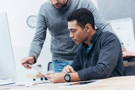 Photo pour Recadrée tir des deux hommes d'affaires en regardant document sur lieu de travail - image libre de droit