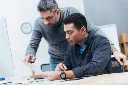 Photo pour Collègues de travail concentré discussion papers sur lieu de travail - image libre de droit