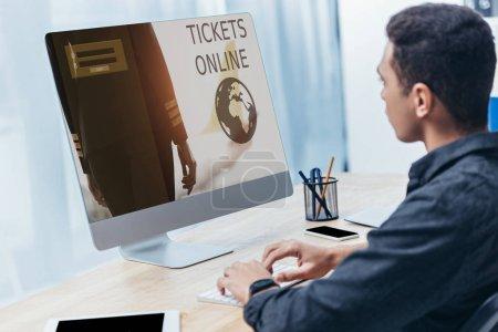 Photo pour Jeune homme d'affaires avec ordinateur de bureau de site Web en ligne de billets sur écran au bureau - image libre de droit