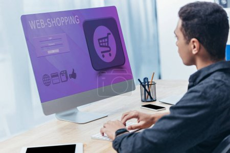 Photo for Young businessman using desktop computer with shopping website on screen in office - Royalty Free Image