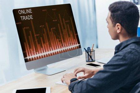 Photo pour Jeune homme d'affaires à l'aide d'ordinateur de bureau avec des graphiques de commerce en ligne sur écran au bureau - image libre de droit