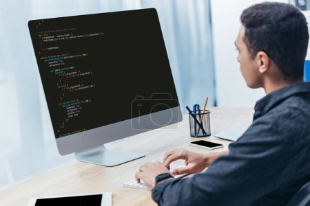 young businessman using desktop computer with html code on screen in office