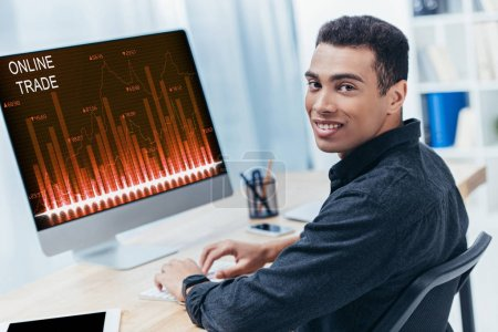 young mixed race businessman using desktop computer with online trade charts and smiling at camera