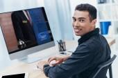 """Постер, картина, фотообои """"молодой смешанной расы бизнесмен с помощью настольного компьютера с веб-сайт сегодня и улыбка на камеру"""""""