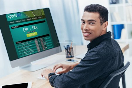 young mixed race businessman using desktop computer with sports bet website and smiling at camera