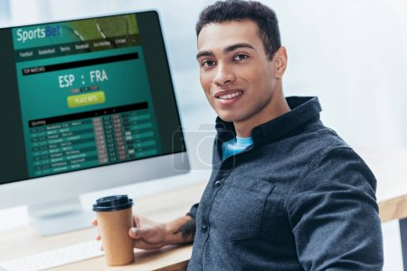 young businessman with coffee to go using desktop computer with sports bet website and smiling at camera