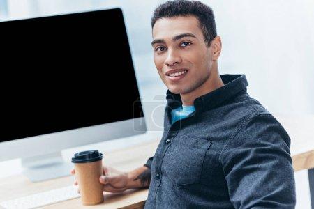 Foto de Joven empresario con café para ir trabajando con el ordenador de sobremesa y sonriendo a cámara - Imagen libre de derechos