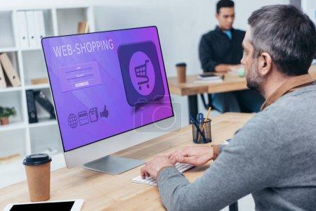 Geschäftsmann mit Desktop-Computer mit Web-Shopping auf dem Bildschirm im Büro