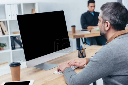 Photo for Businessman using desktop computer with blank screen in office - Royalty Free Image