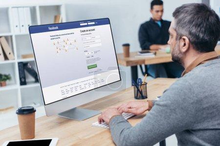 businessman using desktop computer with facebook website on screen in office