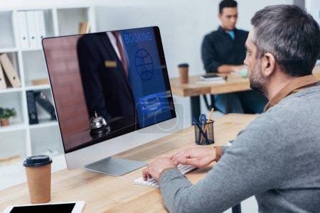 Photo pour Homme d'affaires à l'aide d'ordinateur de bureau avec le site Web de réservations sur écran au bureau - image libre de droit