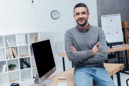 Foto de Apuesto empresario barbudo sentado con los brazos cruzados en el escritorio y sonriendo a la cámara en la oficina - Imagen libre de derechos