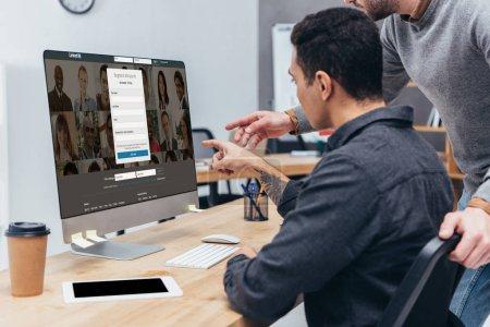 recortar foto de compañeros de trabajo con computadora de escritorio con el sitio web de linkedin en pantalla en la oficina
