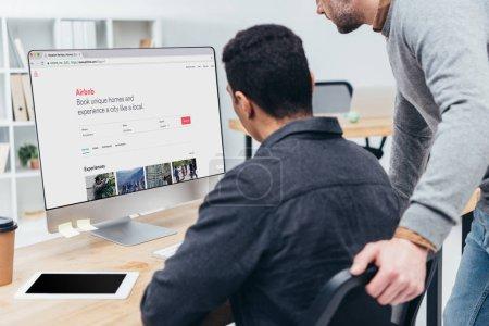 Photo pour Recadrée tir de collègues de travail à l'aide d'ordinateur de bureau avec le site airbnb sur écran au bureau - image libre de droit