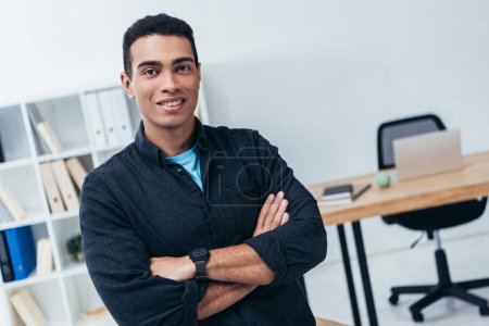 Photo for Handsome young businessman standing with crossed arms and smiling at camera in office - Royalty Free Image
