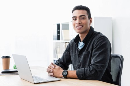 happy young mixed race businessman sitting at table with laptop and smiling at camera in office