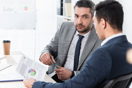 serious bearded businessman looking at young male colleague holding document with charts in office