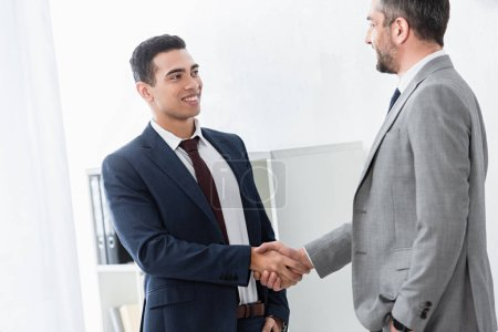 Photo for Professional businessman shaking hands and smiling each other in office - Royalty Free Image