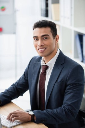 handsome young businessman working with desktop computer and smiling at camera in office