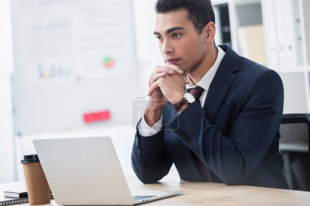 Photo for Confident young businessman sitting at table with laptop and looking away in office - Royalty Free Image